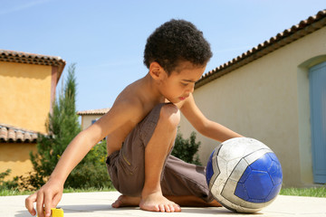 Little boy sitting with a ball
