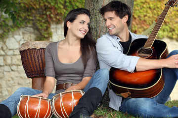 Couple playing drums and a guitar under a tree