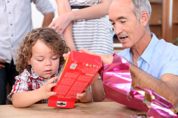 Little boy opening a gift from his grandfather