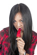 Asian woman biting red hot pepper