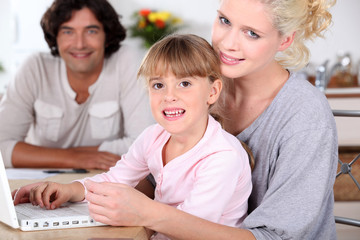 Parents and daughter using a laptop computer