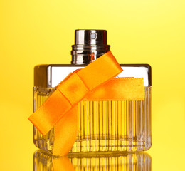 Perfume bottle with orange bow on yellow background