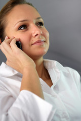 Woman in white shirt making a phone call