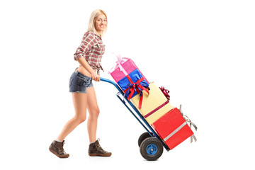 Female manual worker pushing a handtruck with presents on it