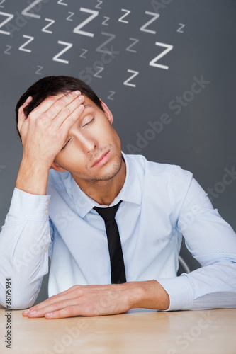 Bored businesspeople: man sitting at desk holding his head. Youn