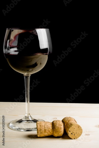 glass of wine near two cork on old wood