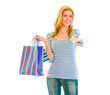 Beautiful teen girl with shopping bags giving credit card