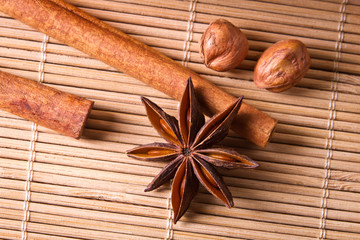 Closeup star anise and nuts on wooden bamboo mat