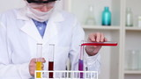 Female scientist mixing chemicals in test tube