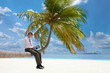 Manager with tablet pc sitting on palm tree