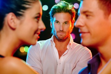 Jealous man looking at flirting couple