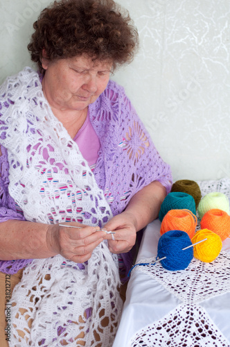 Middle-aged woman knitting a shawl