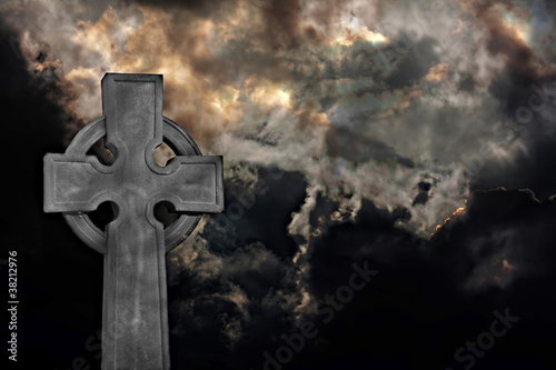 Graveyard cross against storm clouds