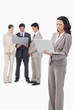 Standing saleswoman with notebook and colleagues behind her