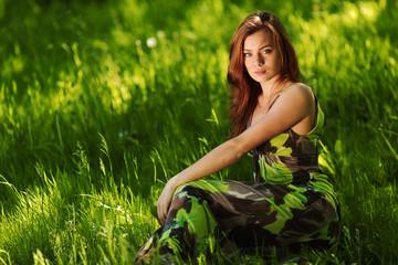 brunette sitting on green grass