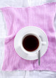 Cup of black coffee on a pink placemat