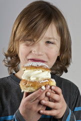 Young boy with a cream bun with almond paste