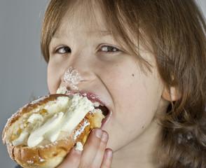 Boy enjoying a cream bun with almond paste