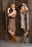 CowGirls with pistol standing in saloon entrance poster