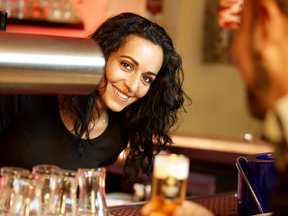 Mediterranean looking bar-maid enjoys her work at a pub