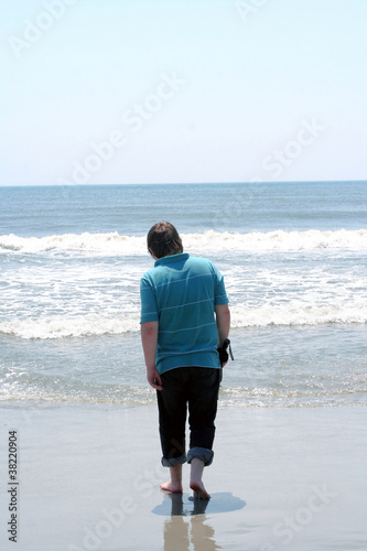 Teen Boy Walking Toward Surf With Closed Umbrella