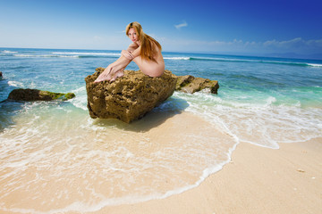 The naked girl on a stone at edge of waves.