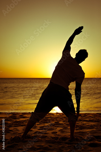 Silhouette of a man stretching on the beach at sunset