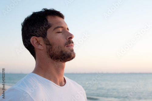 Handsome man deep breathing on the beach