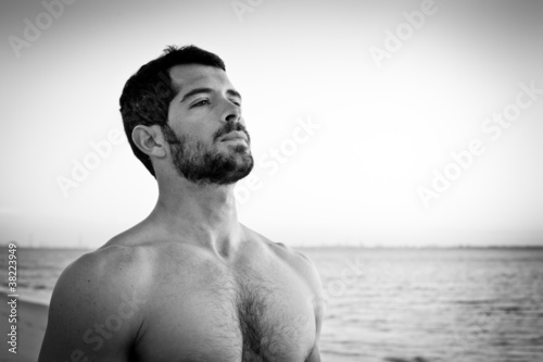 Muscular man on the beach. Black and white portrait.