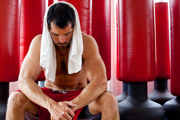 Muscular man sweating, sitting with towel on his shoulders