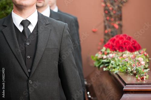 Leinwanddruck Bild coffin bearer carrying casket at funeral