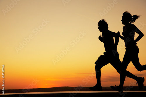 Young couple run together on a sunset
