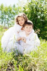 Beautiful little girl and boy, with bush blossoming apple-tree