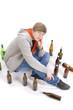 Junger Alkoholiker sitzt am Boden