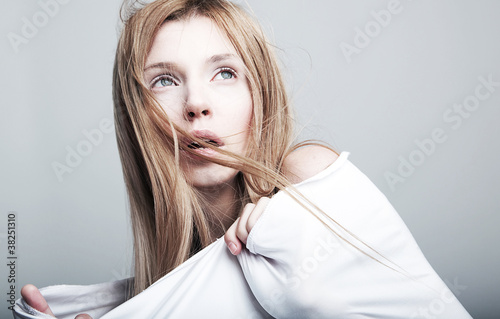 Frightened lovely woman blonde in white clothes