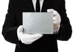 Butler holding blank silver invitation card with copy space