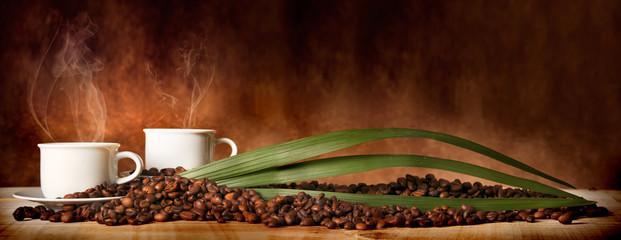 Caffè in tazza, con chicchi sparsi sulla tavola