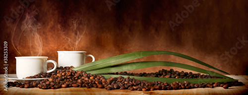 Foto op Plexiglas Cafe Caffè in tazza, con chicchi sparsi sulla tavola