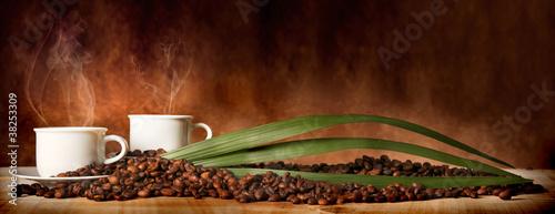 Fotobehang Cafe Caffè in tazza, con chicchi sparsi sulla tavola
