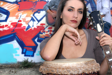 Female band member with guitar and bongo