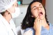 Patientin zeigt Zahnarzt wo es weh tut