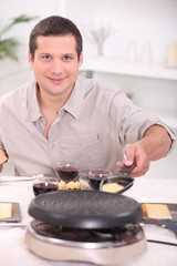 Man cooking raclette at the table