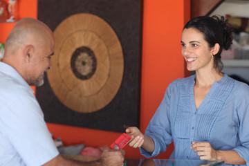 Frau nimmt in einer Boutique eine Kreditkarte entgegen