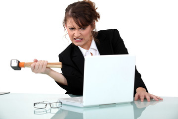 Woman threatening computer with hammer