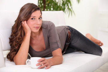 A brunette laying on her sofa drinking a coffee.