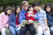 Happy interracial family enjoying day at park with disabled son