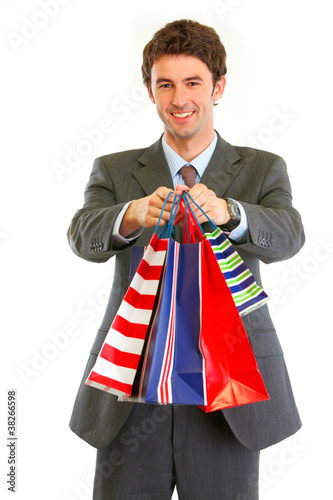 Portrait of smiling businessman with shopping bags