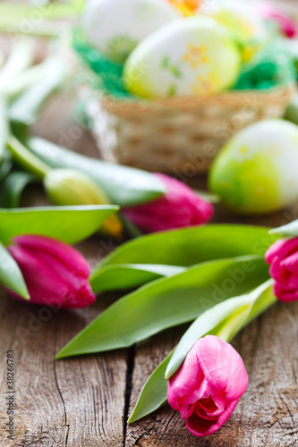 easter basket,eggs and tulips on wooden board
