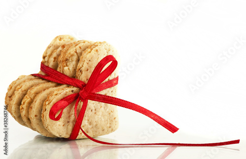 Cookies-hearts connected by a red tape on a white background