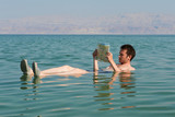 man reads a book in the Dead Sea